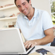 Young man working with laptop computer — Stock Photo