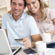 Stock Photo: Young couple using credit card on internet