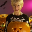 Halloween party with a boy holding carved pumpkin — Stock Photo