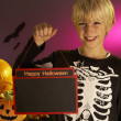 Halloween party with a boy child holding sign — Stock Photo