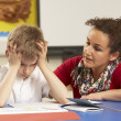 Stressed Schoolboy Studying In Classroom With Teacher — Stock Photo #11879595