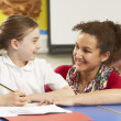 Schoolgirl Studying In Classroom With Teacher - Stock Photo