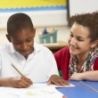 Schoolboy Studying In Classroom With Teacher - Stock Photo