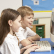 Schoolchildren In IT Class Using Computer - Foto Stock