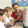 Schoolchildren In IT Class Using Computer with teacher — Stock Photo