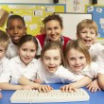 Schoolchildren in IT Class Using Computers with teacher — Stock Photo #11879674