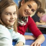 Schoolgirl Studying In Classroom With Teacher — Stock Photo #11879743