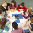 Stock Photo: Schoolchildren Working Together At Desk With Teacher