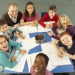 Schoolchildren Working Together At Desk With Teacher — Stock Photo #11879830