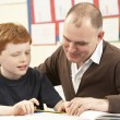 Male Pupil Studying in classroom with teacher — Stock Photo
