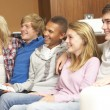Group Of Teenage Friends Sitting On Sofa At Home Watching TV - 图库照片