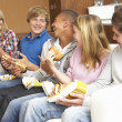 Group Of Teenage Friends Sitting On Sofa At Home Eating Fast Foo — Stock Photo #11879985