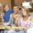 Group Of Teenage Friends Sitting On Sofa At Home Eating Pizza — Stock Photo #11879987