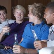 Group Of Teenage Boys Sitting On Sofa At Home Watching Drinking — Stock Photo