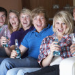 Group Of Teenage Friends Sitting On Sofa At Home Watching Drinki — Stock Photo