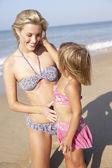 Matka hraje s mladou dívku na pláži — Stock fotografie