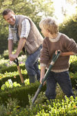 Young man with child working in garden — Stock Photo
