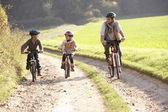Young father with children ride bikes in park — Stockfoto
