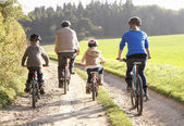 Young parents with children ride bikes in park — Stok fotoğraf