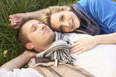 Young couple lying together on grass — Stock Photo