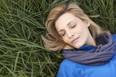 Young woman napping alone on grass — Stock Photo