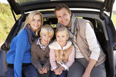 Young family pose together at rear of car — Stock Photo