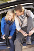Young couple tie boots at rear of car — ストック写真