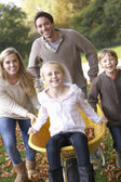 Family having fun with autumn leaves in garden — Stock fotografie