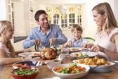 счастливая семья, имея жареный куриный ужин на столе — Стоковое фото