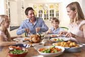 Happy family having roast chicken dinner at table — ストック写真