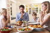 Family Saying Prayer Before Eating Roast Dinner — Stock Photo