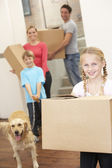 Family with dog on moving day carrying cardboard boxes — Stock Photo