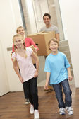 Family happy on moving day carrying cardboard boxes — Stock Photo