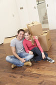 Young couple on moving day sitting with cardboard boxes — Stock Photo