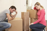 Young couple looking upset among boxes — Stock Photo