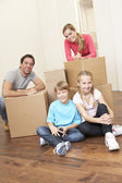 Young family on moving day looking happy among boxes — Stock Photo