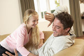 Young father with girl having fun on sofa — Fotografia Stock