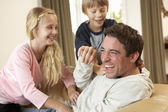 Young father with children having fun on sofa — Stock Photo