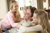 Familia joven feliz jugando juntos en el sofá — Foto de Stock