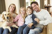 Happy young family sitting on sofa holding a dog — Stok fotoğraf