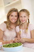 Young woman with child splitting pea in kitchen — Stock Photo