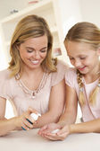 Mother putting sanitizer on young girl's hands — Stock Photo