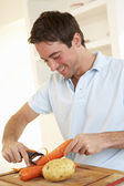 Happy young man peeling vegetable in kitchen — Stock Photo