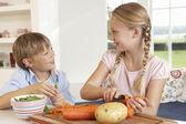 Mutlu çocuklar mutfakta sebze soyma — Stok fotoğraf