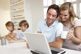 Happy young family looking and reading a laptop computer — Stock Photo