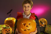 Halloween party with a boy child holding carved pumpkin — Stock Photo