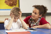 Stressed Schoolboy Studying In Classroom With Teacher — Stock Photo