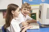 Crianças em idade escolar na mesma classe usando o computador — Foto Stock