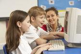 Crianças em idade escolar na mesma classe usando o computador com o professor — Foto Stock