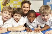 Crianças em idade escolar na mesma classe usando computadores com professor — Foto Stock